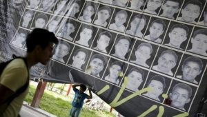 A child stands underneath a banner showing the photographs of the 43 missing students of the Ayotzinapa teachers' training college.   Photo: Reuters